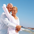 An aged couple on a vacation caring for each other - Stock Photo