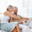 A senior retired couple working on a laptop - Stock Photo