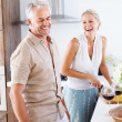 Senior couple preparing food in the kitchen - Stock Photo