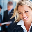 Closeup of a happy business woman with colleagues at the back - Stock Photo
