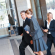 Group of business colleagues walking into their office building - Stok fotoğraf