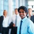 Asian business man smiling with his colleagues at the back - Stock Photo