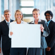 Royalty-Free Stock Photo: Business women holding a blank board with the men behind them