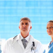 Royalty-Free Stock Photo: Two professional doctors on bluish background looking away