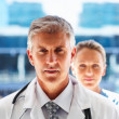 Senior medical doctor with colleague in the background - Stock Photo