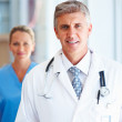 Royalty-Free Stock Photo: A Mature doctor in uniform smiling with assistant in the backgro