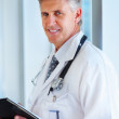 Royalty-Free Stock Photo: A smart confident mature doctor, smiling