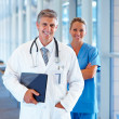 Portrait of professional doctors standing together and smiling - Stock Photo