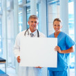 Royalty-Free Stock Photo: Professional doctors holding a blank board