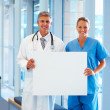 Team of doctors holding a blank billboard - Stock Photo