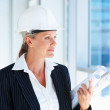 A pretty female architect holding blueprints looking away - Foto Stock