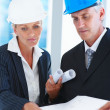 Couple of engineers busy discussing on a project - Stock Photo