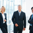 Happy team of business associates at the hallway - Stock Photo