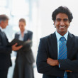 Royalty-Free Stock Photo: Happy business man smiling while his colleagues discuss at the b