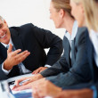 Senior business man speaking to his associates at a meeting - Stock Photo