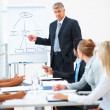 Presentation: Business man at a meeting - Stock Photo