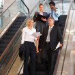 Sophisticated business on escalator, discussing business - Stock Photo