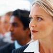 Business woman looking away while in line with colleagues - Stock Photo