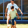 Young boy and his dad playing football - Stock Photo