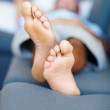 Royalty-Free Stock Photo: Closeup of feet of man relaxing on sofa