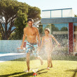 Father and daughter playing at the sprinkler, cooling off - Foto de Stock