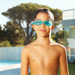 Happy young boy wearing swimming goggles by the pool, outside - Stok fotoğraf