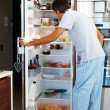 Hunger: Mature man opening the refrigerator door - Stock Photo