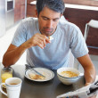 Senior man enjoying a healthy breakfast and the newspaper - Stock Photo