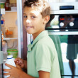 Royalty-Free Stock Photo: Young boy stealing milk from the fridge