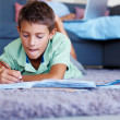 Royalty-Free Stock Photo: Smart boy studying on the floor while father in the background