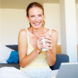 Royalty-Free Stock Photo: Sexy woman using laptop computer while drinking cup of coffee