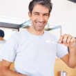 Smiling: Handsome man showing toothbrush - Stock Photo
