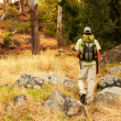 Adventurous young guy trekking in the bush - Stock Photo
