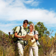 Couple with  backpacks looking at a map - Stock Photo
