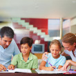 Children with their parents assisting them in the homework - Stock Photo