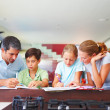 Helpful parents helping their children with their homework - Stock Photo