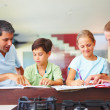 Royalty-Free Stock Photo: Parents assisting their children to do their homework