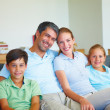 Happy family sitting in the living room smiling - Foto de Stock  