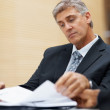 Royalty-Free Stock Photo: Senior business man reading through files at work