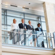 Royalty-Free Stock Photo: Successful business team standing by a glass railing