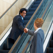 Royalty-Free Stock Photo: Business man shaking a colleagues hand by the escalator