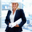 Portrait of a female architect wearing a hardhat, holding bluepr - Stockfoto