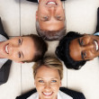 Royalty-Free Stock Photo: Happy team of colleagues smiling while lying on the floor