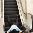 Young business man fallen at the escalator - Stock Photo
