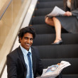 Royalty-Free Stock Photo: Happy business man sitting on the escalator reading newspaper