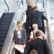 Business on the escalator, focus on woman - Stok fotoğraf