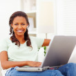 African American woman using a laptop at home - Stock Photo