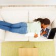 Top view of an African American female lying on sofa and using a - Stock Photo