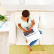 Top view of a woman on sofa using a laptop - Stock Photo