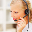 Closeup of a woman wearing headset in office - Stock Photo